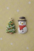 黄色地に白い星がある背景の上に雪だるまとクリスマスツリー