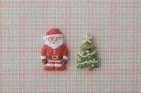 赤、緑、黄色のチェック柄の上にサンタとクリスマスツリー