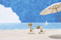 真夏の砂浜を走る二人の子供