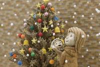 クリスマスツリーの前で降って来る雪を見上げる母親と母親に抱かれた子供 20041000487| 写真素材・ストックフォト・画像・イラスト素材|アマナイメージズ