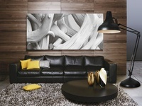 A black leather sofa and a coffee table with a floor lamp in