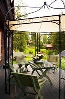 Garden furniture on a wooden terrace under a canopy with a m