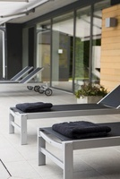 Designer loungers on a grey-tiled terrace in front of a hous