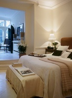 A traditional, open plan bedroom, double bed, ottoman, open