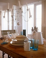 A chandelier with white candles above a wooden table set wit