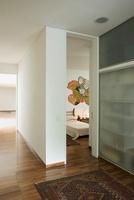 A modern hallway with parquet flooring an an open bedroom do
