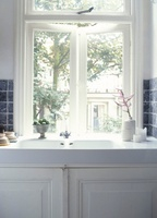 An antique porcelain sink under the window with a white cupb