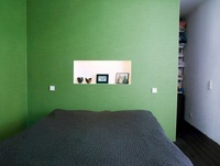 A double bed in a bedroom with green walls