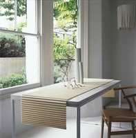 A grey table with a table runner in front of a window