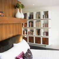 A bed with an upholstered headboard and a contemporary shelf