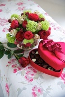 An open box of chocolates and a bunch of flowers on a floral