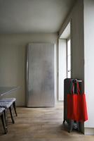 Simple closet and red bag hanging on a radiator in a minimal