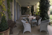 Light gray wicker furniture and planters in the loggia of a