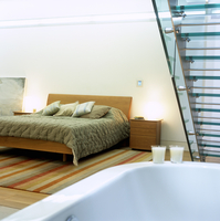 A bedroom with a bathtub and glass stairs