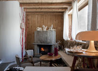 Open fireplace in corner of rustic room with furniture in a