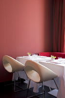 Set tables for two with white and deep pink designer chairs