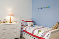 Child's bedroom with white, rustic furniture against blue-pa