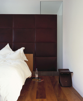 Bed against cushioned wall covered in brown leather in desig