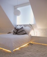 Double bed and sideboard with integrated, indirect lighting