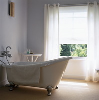 Free-standing vintage bathtub in front of window in minimali