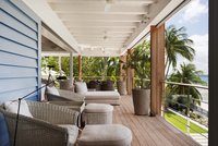 Roofed balcony with comfortable seating and view of palm tre