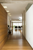 View along corridor with wide wooden door into open-plan, li