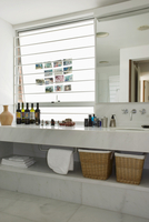 White marble bathroom with bottles on long washstand and pho
