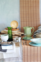 Crockery, wooden chopping boards and table linen in natural