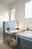 Blue-tiled bathtub with half-height partition in simple bath