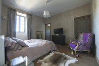 Simple bedroom with bed in front of window and Rococo-style