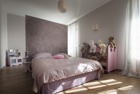 Double bed against lilac partition and soft toys on half-hei