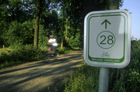 Cyclist and signpost of cycle route Brugse Ommeland, Beernem, Belgium . (Photo by: Arterra/UIG)