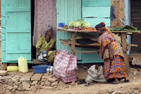 Black woman buying vegetables from street vendor in the city Kampala, Uganda, Africa. (Photo by: Arterra/UIG)