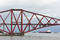 Oil tanker sailing under the Forth Railway Bridge / Forth Rail Bridge, a bridge over the Firth of Forth near Edinburgh, Scotland