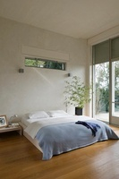 Shutters at windows and low Hugues wooden bed with lilac cov