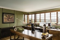 Narrow wooden table and work desk in study with green silk l