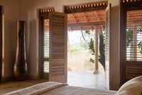 Double doors open from bedroom to veranda of Goan beach hous