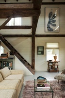 Open plan seating area with wooden ceiling beams and stairca