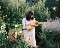 A mother holds her son in her arms in a garden. 20055003800| 写真素材・ストックフォト・画像・イラスト素材|アマナイメージズ