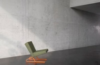 green chair infront of concrete wall