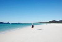 A Young Women Walking On A White Sandy Beach
