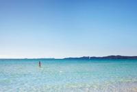A Young Women In A Bikini Walking Into The Sea