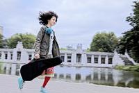 Girl Running Carrying Guitar In Case 20055008130| 写真素材・ストックフォト・画像・イラスト素材|アマナイメージズ