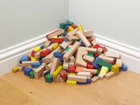 A Pile Of Wooden Children'S Blocks In The Corner Of A Green