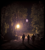 People Walking On A Road With Trees And A Light In The Backg