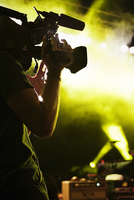 A Camera Man On Stage Filming A Rock Concert.