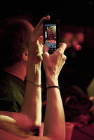 A Lady Taking A Picture With Her Smart Phone At A Rock Conce