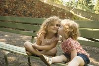 Young Girl Giving Older Sister Kiss On Cheek