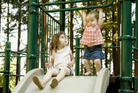 Young Sisters On Slide At Park