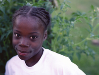 Young Girl Of African-American Appearance Playing In A Green